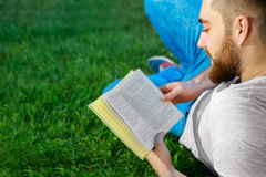 Young man reading a book in park Royalty Free Stock Photography
