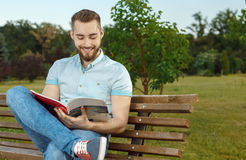 Young man reading book in the park Royalty Free Stock Photo