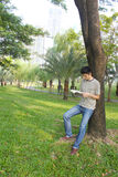 Young man reading the book in the park. Stock Images