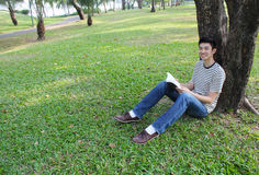 Young man reading the book in the park. Stock Photo