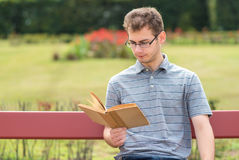 Young man reading a book in park Royalty Free Stock Image
