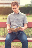 Young man reading a book in park Royalty Free Stock Photo