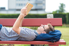 Young man reading a book in park Stock Photos