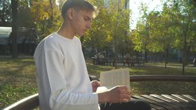 Young man is reading book it the park. Young man is reading book at the park. The boy is at the city park with a book. Spending time outdoor in modern city stock video footage