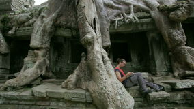 Young man reading book in preah khan temple, angkor stock video footage