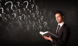 Young man reading a book with question marks coming out from it Stock Photos