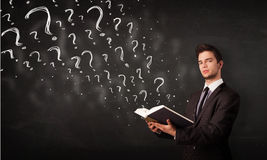 Young man reading a book with question marks coming out from it Royalty Free Stock Images