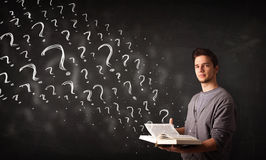 Young man reading a book with question marks coming out from it Stock Photography