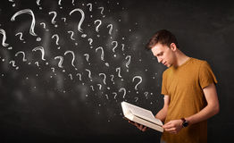 Young man reading a book with question marks coming out from it Royalty Free Stock Photo
