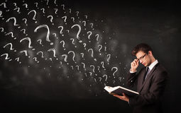 Young man reading a book with question marks coming out from it Royalty Free Stock Photos