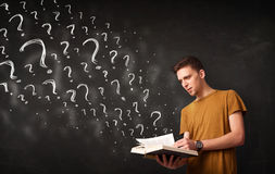 Young man reading a book with question marks coming out from it Royalty Free Stock Image