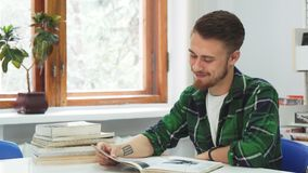 A cute guy laughs at what he read in the book. A young man is reading a book. He read something funny and laughs at it. Near him lies a lot of books. Young guy stock video footage