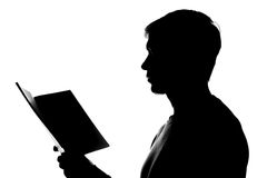 Young man reading a book - silhouette Royalty Free Stock Photography