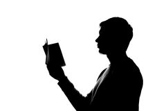 Young man reading a book - silhouette Stock Image