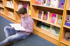 Young man reading book while sitting by bookshelf Stock Photo