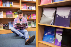 Young man reading book while sitting on floor Royalty Free Stock Photos