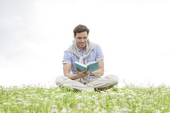 Young man reading book while sitting on grass against sky Royalty Free Stock Photo