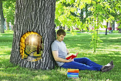 Young man reading a book sitting on the green grass leaning on a tree in the Park. The concept of summer vacation and camping. Outdoor library. Surrealism and Royalty Free Stock Images