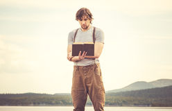 Young Man reading book standing outdoor Royalty Free Stock Image
