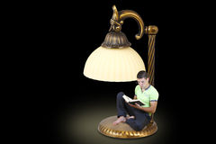 Young man reading a book under a table lamp. Young man reading a book under the desk lamp on a black background Royalty Free Stock Photo