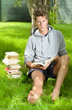 Young man reading a book under a tree Stock Photos