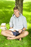 Young man reading a book under a tree Royalty Free Stock Image