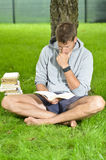 Young man reading a book under a tree Royalty Free Stock Images