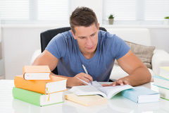 Young Man Reading Books Stock Images
