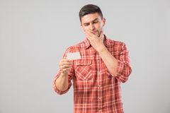 Young man reading business card. Isolated on gray background Royalty Free Stock Photo