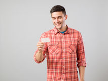 Young man reading business card. Isolated on gray background Royalty Free Stock Image