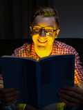 Young man reading comedy. In dark room Stock Photography