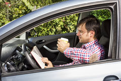 Young man reading and drinking coffee while driving royalty free stock image