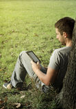 Young man reading e-book Stock Photo