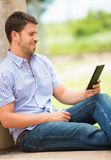 Young man reading E-book outside Stock Photos