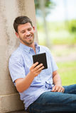 Young man reading E-book outside Royalty Free Stock Photography