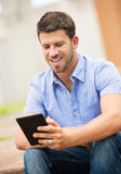 Young man reading E-book outside Stock Photo