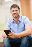Young man reading E-book outside Royalty Free Stock Photos
