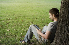 Young man reading e-book Stock Image