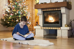 Young man reading front of fireplace at Christmas Stock Image