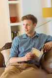 Young man reading on his couch Stock Photography