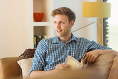 Young man reading on his couch Royalty Free Stock Images