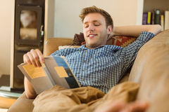 Young man reading on his couch Royalty Free Stock Photos