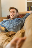 Young man reading on his couch Stock Image
