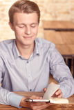 Young man reading his notes in cafe Stock Photos