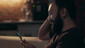 Young man reading his tablet in the dark stock video