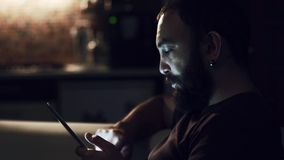 Young man reading his tablet in the dark stock footage