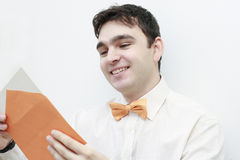 Young man reading a letter smiling Royalty Free Stock Photos