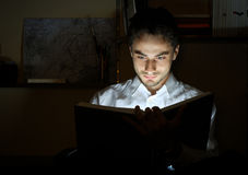 Young man reading in a library stock image