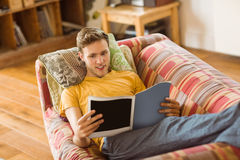 Young man reading magazine on his couch Royalty Free Stock Images