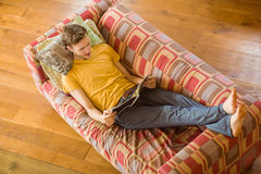 Young man reading magazine on his couch Stock Photography